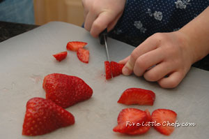 Little Chef D cutting strawberries