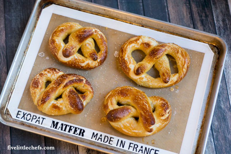 This easy homemade buttery soft pretzels recipe is loved by many! We have made it easy to understand how to make these with step by step instructions.They taste just like the mall but made at home for a great snack. fivelittlechefs.com