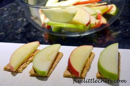 Peanut Butter Apple Crackers from fivelittlechefs.com is a simple snack kids can customize themselves! Go on, play with your food! #peanutbutter #apple #kidscooking